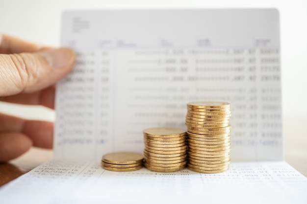 Oszczędność pieniędzy i koncepcja finansowa. zbliżenie stos złotych monet na książeczkę bankową ręką człowieka, trzymając książkę.