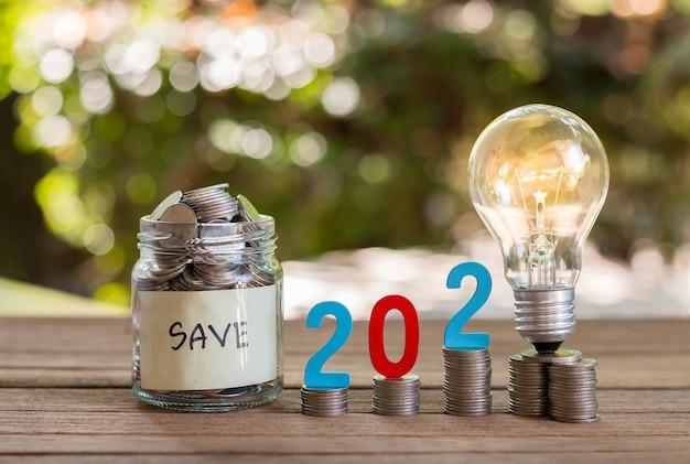 Oszczędność pieniędzy i monet w szklanej butelce na drewnianej podłodze. koncepcja inwestycji na przyszłość. z tłem bokeh