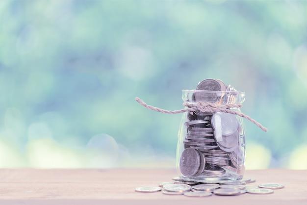 Oszczędność pieniędzy koncepcja, monety pieniądze w szklanym słoju na drewnianym stole