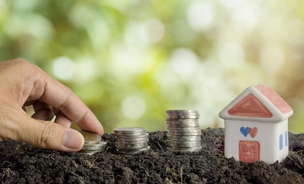 Oszczędność pieniędzy na budowę koncepcji domu, domu i monet w glebie