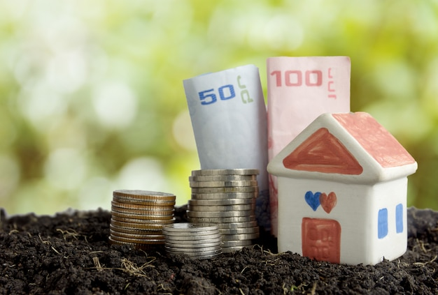 Oszczędność pieniędzy na budowę koncepcji domu, domu i pieniędzy w glebie