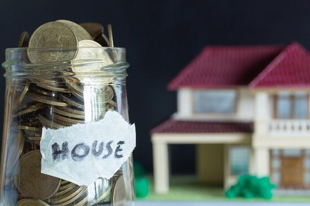 Oszczędność pieniędzy na dom w szklanej butelce.