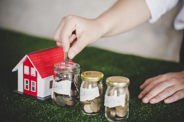 Oszczędność pieniędzy na dom w szklanej butelce