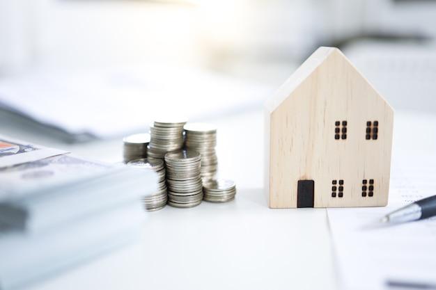 Oszczędność pieniędzy na inwestycje w nieruchomości ze stosem monet na zakup domu i pożyczki w celu przygotowania się do przyszłej koncepcji finansowej lub ubezpieczeniowej