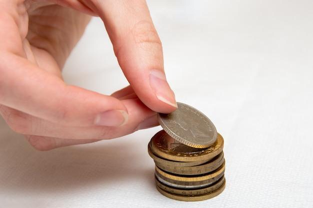 Oszczędność pieniędzy, ręka wkłada monety z różnych krajów w stos, białe tło, zbliżenie.
