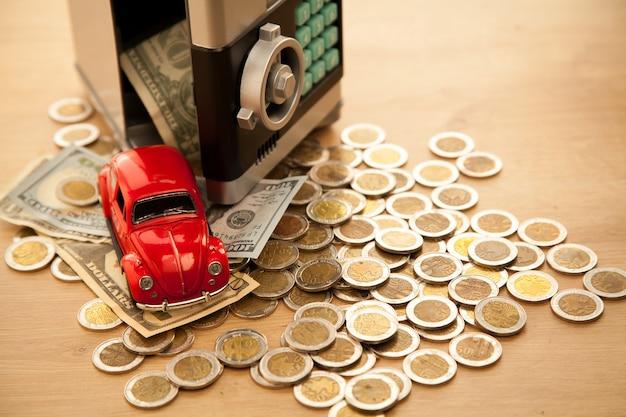 Oszczędności na samochodzie. spadające pieniądze z sejfu.