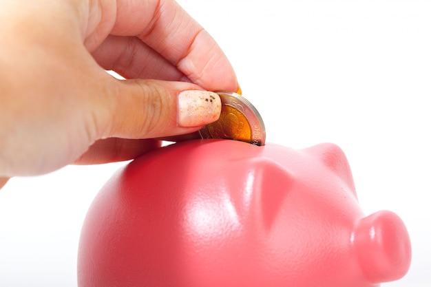 Oszczędności - skarbonka i ręka z monetą