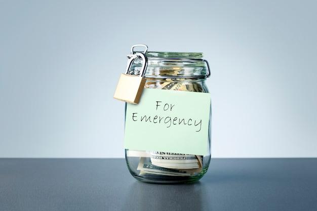 Oszczędności w nagłych wypadkach napisane na słoiku z pieniędzmi w postaci banknotów dolarów. koncepcja oszczędzania pieniędzy na deszczowy dzień.