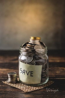 Oszczędności wpłacają monety do przezroczystej szklanej butelki