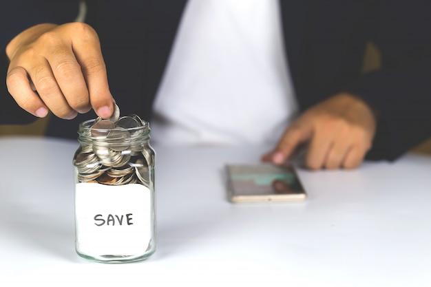 Oszczędności zdeponować monety w butelce z przezroczystego szkła, miejsca kopiowania.