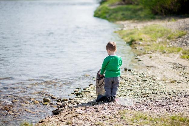 Oszczędź środowisko, mały chłopiec zbierający śmieci i plastikowe butelki na plaży i wyrzucany do śmieci.