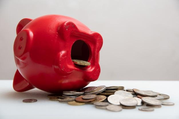 Oszczędzać pieniądze. potrzebujesz otwartej skarbonki z monetami, rozproszonymi monetami z różnych krajów, na białym tle, z bliska.