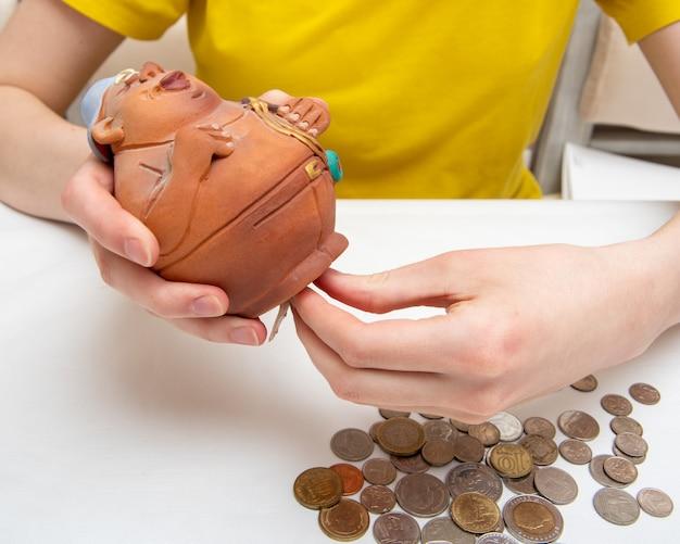 Oszczędzać pieniądze. ręka wyciąga monety. potrzebujesz otwartej skarbonki z monetami, rozproszonymi monetami z różnych krajów, na białym tle, zbliżenie