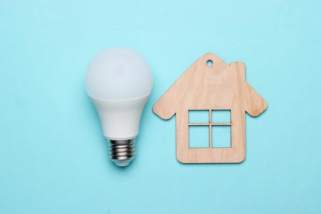 Oszczędzaj koncepcję energii. koncepcja domu ekologicznego. mini dom i żarówka energooszczędna na niebieskim tle