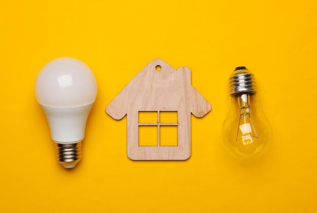 Oszczędzaj koncepcję energii. koncepcja domu ekologicznego. mini domek, żarówka i energooszczędna żarówka na żółtym tle