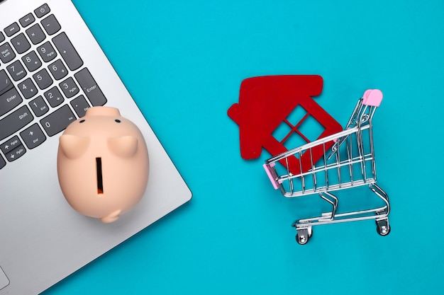 Oszczędzaj na mieszkanie. laptop, skarbonka, wózek na zakupy z figurką domu, portfel na niebiesko