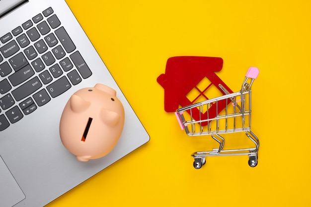 Oszczędzaj na mieszkanie. laptop, skarbonka, wózek na zakupy z figurką domu, portfel na żółto