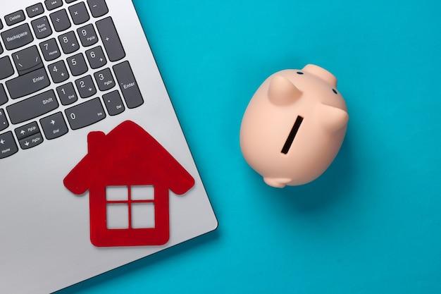 Oszczędzaj na mieszkanie. laptop, skarbonka z domową postacią na niebiesko