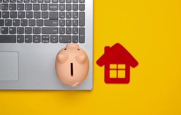 Oszczędzaj na mieszkanie. laptop, skarbonka z domową postacią na żółto