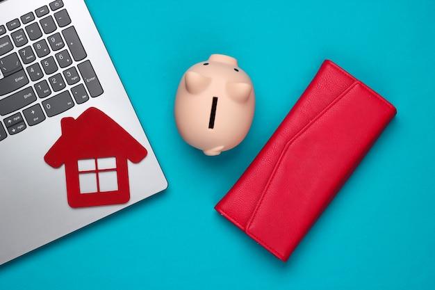 Oszczędzaj na mieszkanie. laptop, skarbonka z figurką domu, portfel na niebiesko