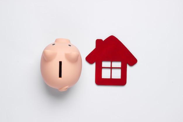 Oszczędzaj na mieszkanie. skarbonka i dom postać na białym tle