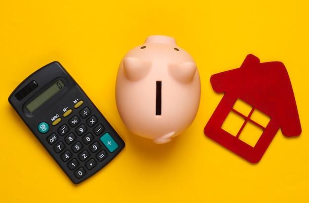 Oszczędzaj na mieszkanie. skarbonka i figura domu, kalkulator na żółto.
