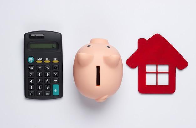 Oszczędzaj na mieszkanie. skarbonka i postać domu, kalkulator na białym tle