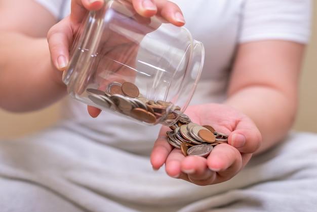 Oszczędzaj pieniądze i konta bankowego dla koncepcji finansów, ręka z monetą na niewyraźnej powierzchni