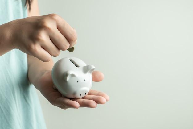 Oszczędzania i biznesu pojęcie, dziewczyna z prosiątko bankiem i monety w domu
