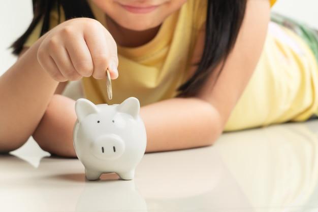 Oszczędzania i biznesu pojęcie, śliczna dziewczyna z prosiątko bankiem i monety w domu