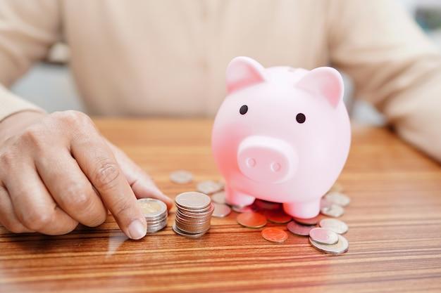 Oszczędzanie pieniędzy, monet i różowa skarbonka.