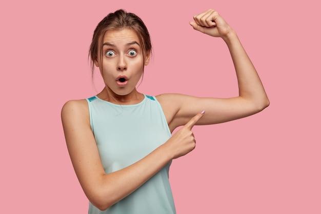 Oszołomiona, emocjonalna kaukaska kobieta z podpuchniętymi oczami, wskazuje na bicepsy, czuje się zszokowana dobrym wynikiem treningu na siłowni, nosi casualową koszulkę, modele na różowej ścianie. strzał poziomy.