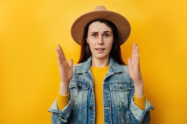 Oszołomiona kobieta w kapeluszu pod wrażeniem pokazuje coś dużego lub dużego, zdumiona ogromnymi rozmiarami, podnosi dłonie i mierzy przedmiot, nosi dżinsową kurtkę, odizolowaną na żółtym tle.