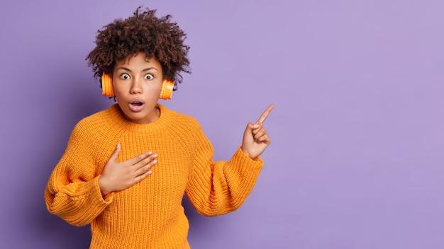 Oszołomiona kobieta wygląda z podpuchniętymi oczami i opuszczoną szczęką, nie może uwierzyć w coś niesamowitego, nosi pomarańczowy sweter i słuchawki w prawym górnym rogu