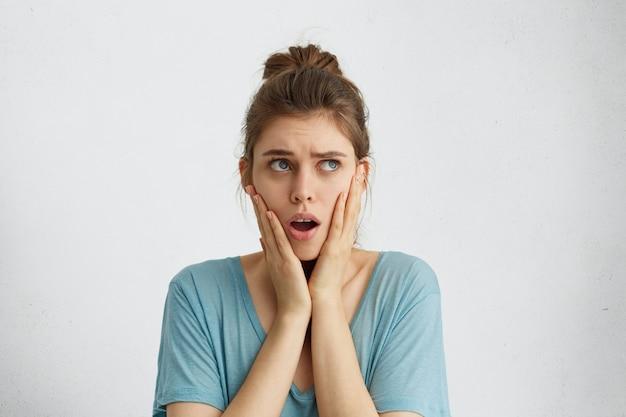Oszołomiona kobieta z zawiązanymi włosami, ubrana w swobodną niebieską bluzkę, trzymająca się za ręce na policzkach, otwierająca usta ze zdziwieniem patrząc w górę