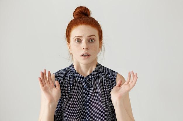 Oszołomiona lub przestraszona młoda dama z rudymi włosami, gestykulująca obiema rękami, o wyrazie zszokowanym i przestraszonym, przestraszona i przerażona czymś przerażającym. język ciała