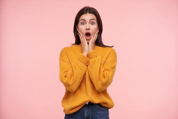 Oszołomiona młoda ładna brunetka kobieta z luźnymi włosami, trzymająca twarz z uniesionymi dłońmi i patrząc zdumiewająco z przodu z szeroko otwartymi ustami, odizolowana na różowej ścianie
