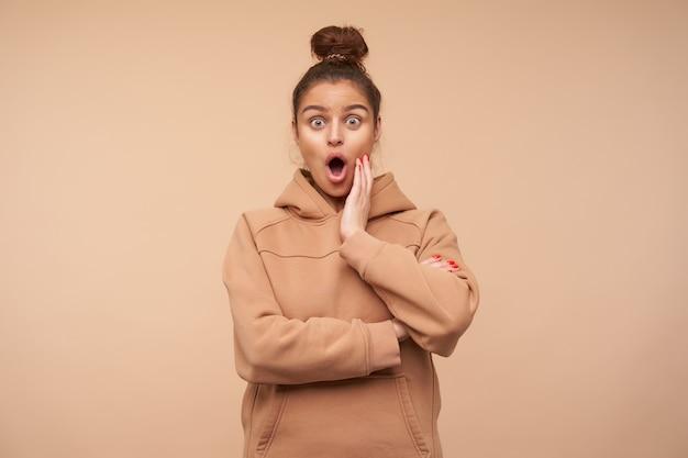 Oszołomiona młoda zielonooka brunetka kobieta z fryzurą w kok z zaskoczeniem unosząc brwi, patrząc zdumiewająco z przodu i trzymając dłoń na policzku, pozując nad beżową ścianą