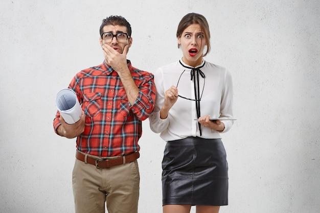 Oszołomiona piękna kobieta zdejmuje okulary, słyszy okropne wieści, a męski kujon patrzy przez okulary z wielkim przykrością,