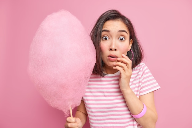 Oszołomiona, przerażona brunetka trzyma słodką watę cukrową, zdziwiona, gdy słyszy, że coś niesamowitego dowiaduje się, ile kalorii ma zamiar zjeść, ma na sobie pasiastą koszulkę odizolowaną od różowej ściany.