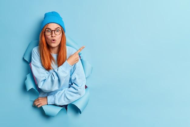 Oszołomiona rudowłosa młoda kobieta wskazuje na prawy górny róg, ukazując miejsce kopiowania z zaskoczonym wyrazem, ubrana w modne młodzieżowe ciuchy.