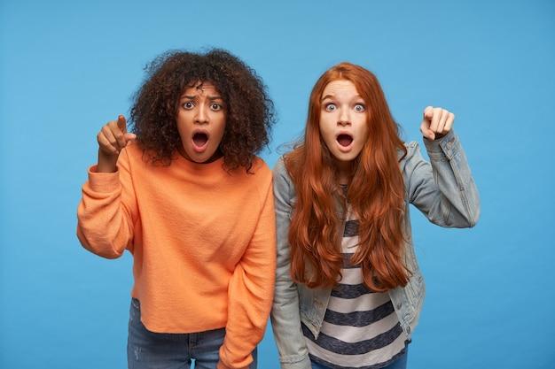 Oszołomione młode atrakcyjne kobiety wskazujące uniesionymi palcami wskazującymi i zaokrąglające ze zdumieniem oczy z otwartymi ustami, odizolowane na niebieskiej ścianie
