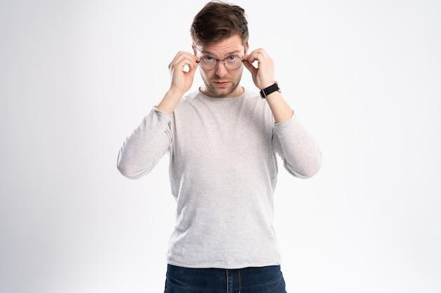 Oszołomiony atrakcyjny młody człowiek patrzy ze zdziwieniem, zdumiony wiadomością.