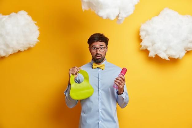 Oszołomiony brodaty ojciec zajęty opieką nad noworodkiem, karmieniem dziecka, trzyma gumowy śliniaczek i butelkę ze sutkiem, zszokowany, gdy żona zostawiła go samego z dzieckiem, pozuje nad żółtą ścianą. koncepcja ojcostwa