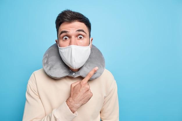 Oszołomiony emocjonalnie dorosły mężczyzna nosi maskę ochronną podczas epidemii koronawirusa podaje zalecenia, jak zachować bezpieczeństwo, prosi o przestrzeganie zasad kwarantanny, nosi poduszkę pod szyję z dala od miejsca kopiowania