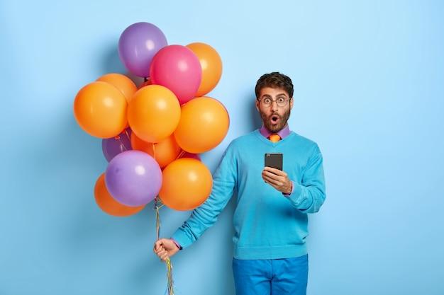 Oszołomiony facet z balonami pozuje w niebieskim swetrze