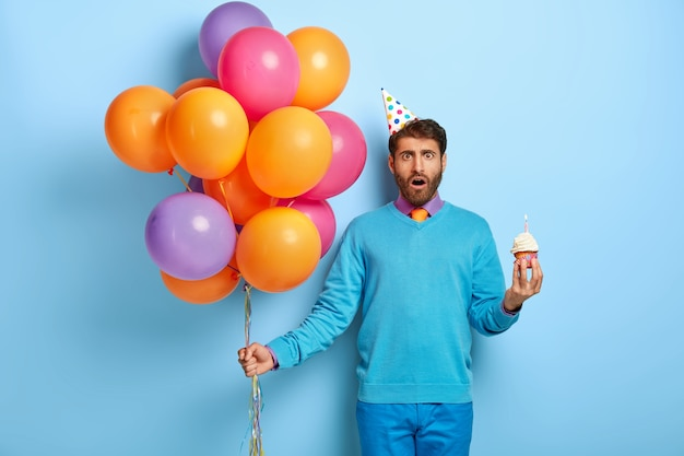 Oszołomiony facet z urodzinową czapką i balonami pozuje w niebieskim swetrze