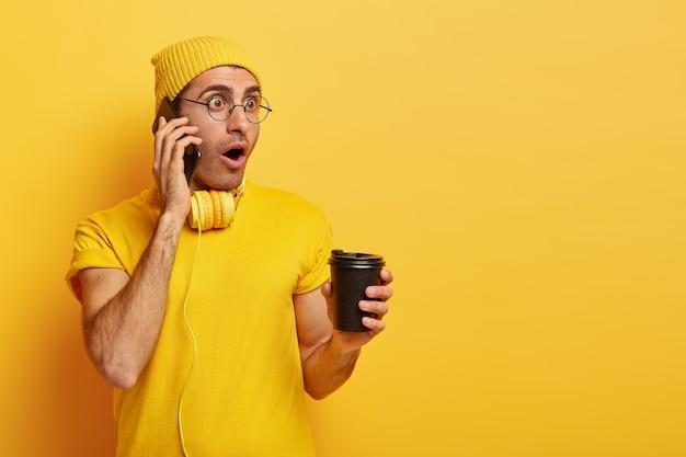 Oszołomiony mężczyzna prowadzi rozmowę telefoniczną, zszokowany najnowszymi wiadomościami, nosi zwykłą koszulkę