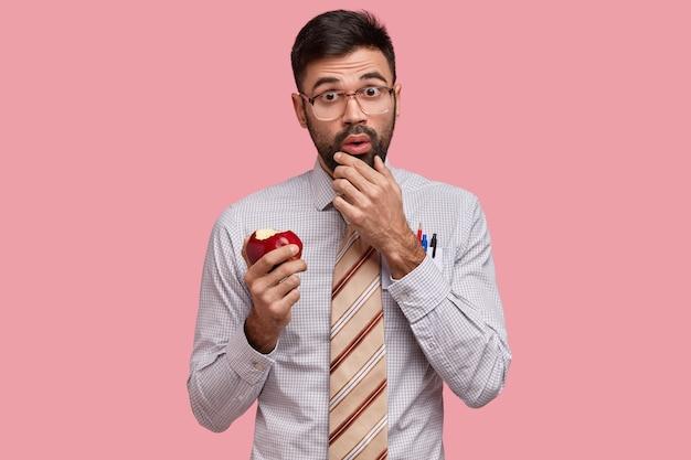 Oszołomiony nauczyciel z grubym włosiem trzyma podbródek, zjada przekąskę między zajęciami, ubrany w formalną koszulę z krawatem