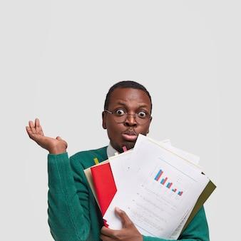Oszołomiony niezdecydowany ciemnoskóry facet wzrusza ramionami i trzyma papiery, podręczniki, czuje się niepewnie